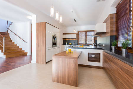 Spacious bright kitchen with wooden units Stock fotó