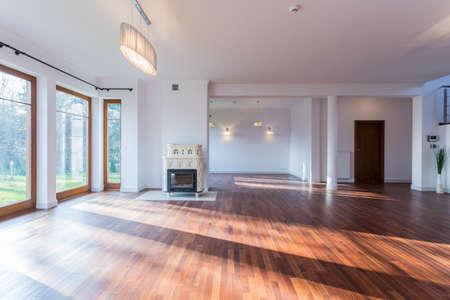 estufa: Imagen de la luminosa sala de estar vacía con piso de madera