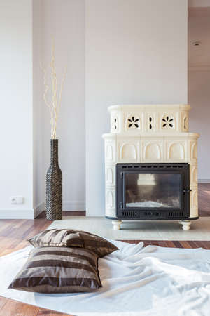 tiled stove: White blanket and pillows ahead of tiled stove Stock Photo