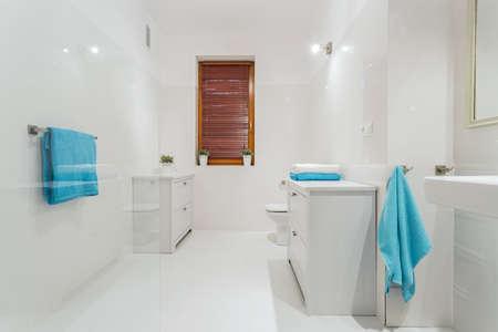 Big white bathroom with blue towels photo