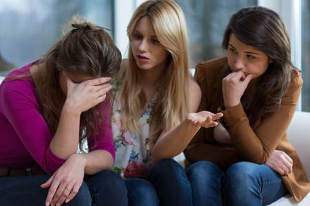 Young broken down woman and her helpful friends Stock Photo