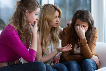 Two young worried girls supporting crying friend