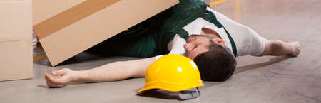 warehouseman: Young male worker lying on the floor in warehouse