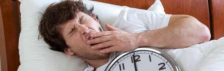 sleepwalking: Man holding a big clock and waking up Stock Photo
