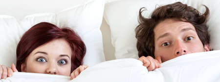 funny faces: Couple with funny faces under the sheet Stock Photo