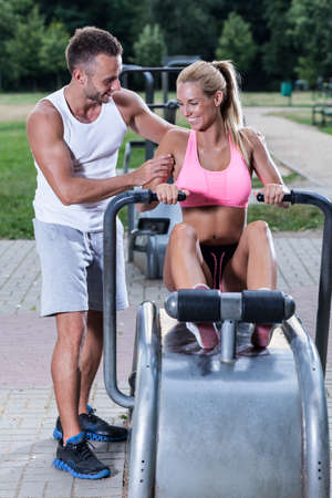 excercise: Women excercise on rowing machine with sport instructor Stock Photo