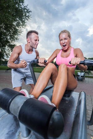 rowing: Intensive workout in outdoor gym with sport instructor Stock Photo
