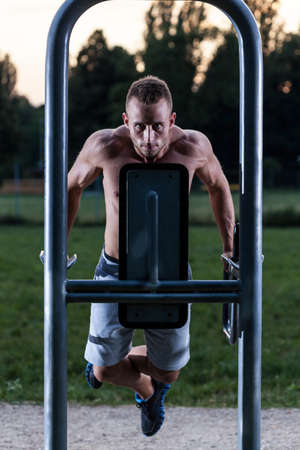 exertion: Muscular man pulling up on excercise machine Stock Photo