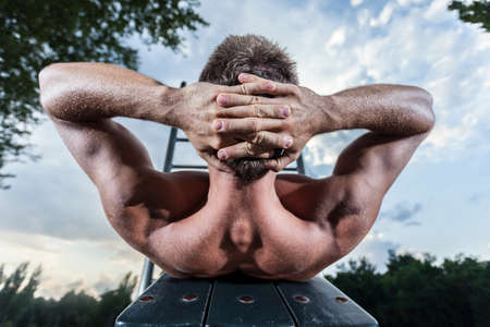 Athlete in park excercises his abdominal muscles