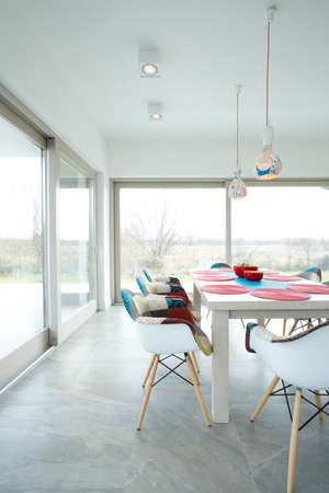 dining table and chairs: Dining room with white table and big windows