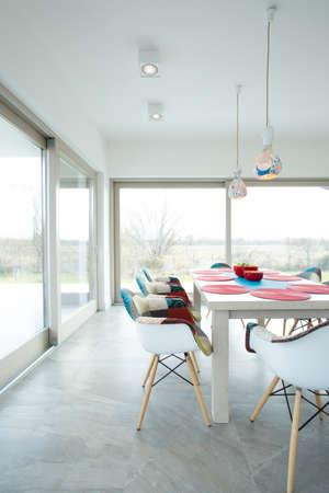 Jídelna s bílým stolem a velkými okny