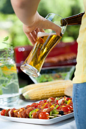 pouring beer: Closeup of woman pouring beer on barbecue Stock Photo