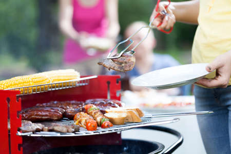 frazzled: Woman dishing out tasty grilled chuck steak Stock Photo