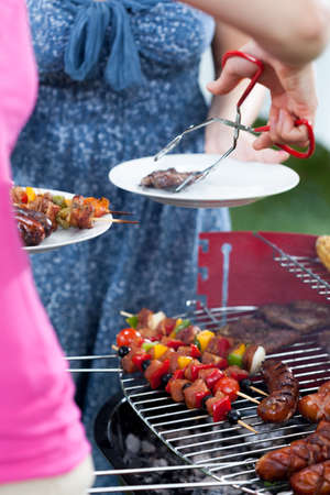 frazzled: Woman serving char-grilled dinner on barbecue party Stock Photo