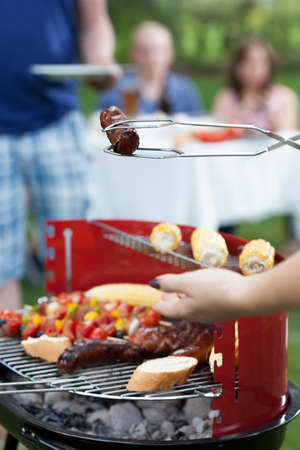 frazzled: Woman taking frazzled sausage from a grill Stock Photo