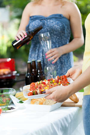 pouring beer: Woman in dress pouring beer during barbecue party