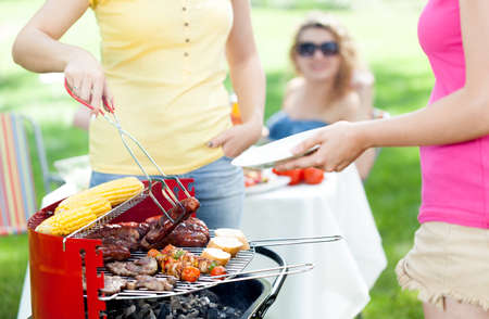 garden party: Host serving woman frazzled sausage on grill party