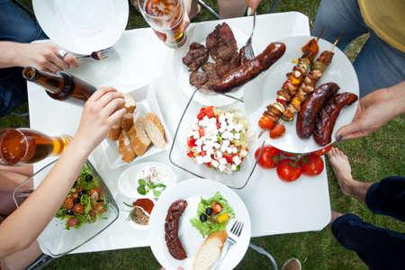 comiendo: Las personas que comen platos a la parrilla en la fiesta de jard�n Foto de archivo