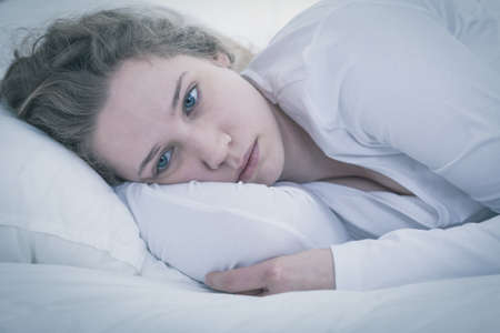 ベッドで横になっている悲しい疲れ女性のクローズ アップ
