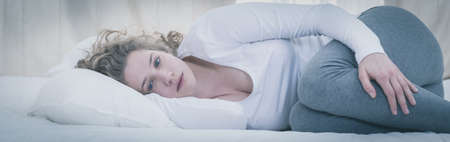 uninterested: Young depressed woman lying alone in her bed Stock Photo