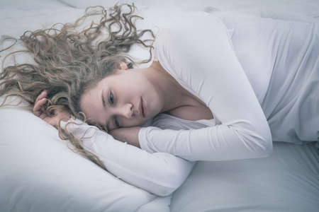 Young attractive woman in deep depression lying alone Imagens