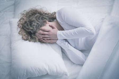 girl bed: Sad girl with depression holding her face in hands Stock Photo