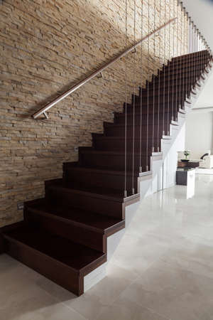 Brick wall and wooden stairs in designed interior