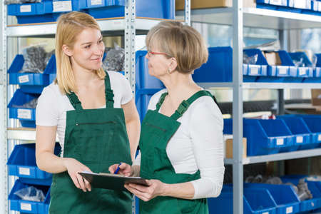 stockroom: Mum and daughter working together in storehouse