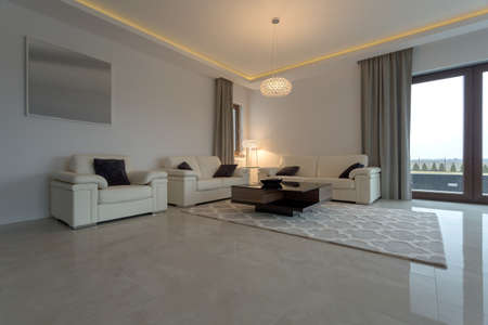a detached living room: Leather cream sofa and armchair in luxury interior