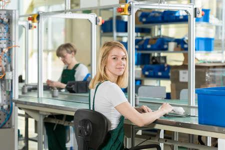 assembly: Belleza mujer joven que trabaja en la línea de producción