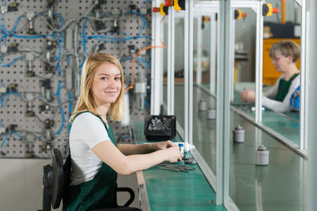 overalls: Young female production worker in manufacturing plant