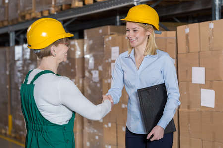 Female supervisor and storage worker shaking hands photo