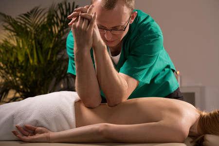 codo: Masajista usando los codos durante el masaje de tejido profundo