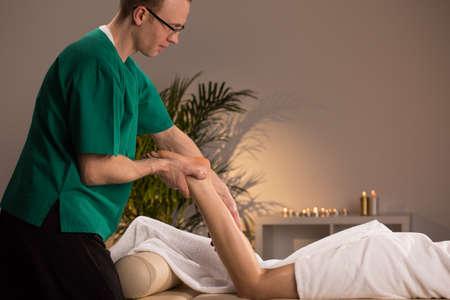 lower limb: Masseur massaging lower limb of young woman