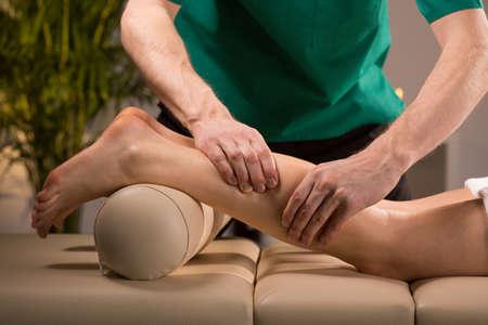 massage jambe: Close-up des mains de masseur p�trissage veau femelle Banque d'images