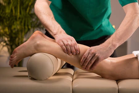 male massage: Close-up of masseurs hands kneading female calf