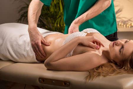 massage homme: Jeune femme de beauté ayant fait le massage abdominal Banque d'images