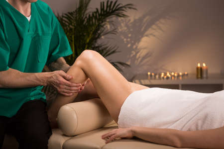 physical therapy: Therapist massaging female leg in massage room