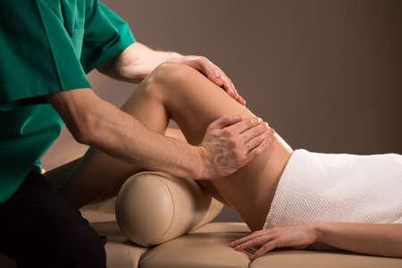 piernas: Primer plano de la masajista de sexo femenino que hace el masaje de la pierna Foto de archivo