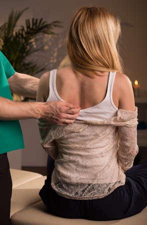 osteopata: Oste�pata que trata mujer joven que tiene dolor de espalda Foto de archivo