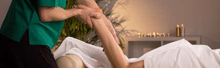 lower limb: Young woman relaxing during leg massage - panorama Stock Photo
