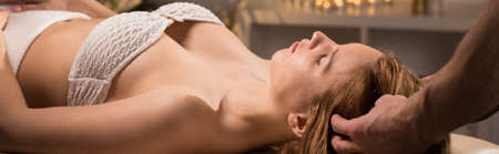 treat acupressure: Woman relaxing during head massage in spa centre