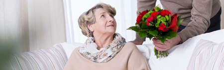 Panorama of senior woman getting anniversary bouquet photo