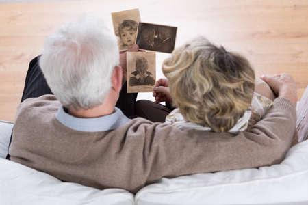 수석 결혼 소파에 앉아 옛날 사진을보고 스톡 콘텐츠