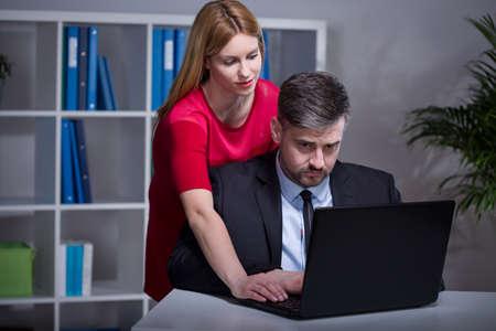 Beautiful female boss helping her older handsome employee