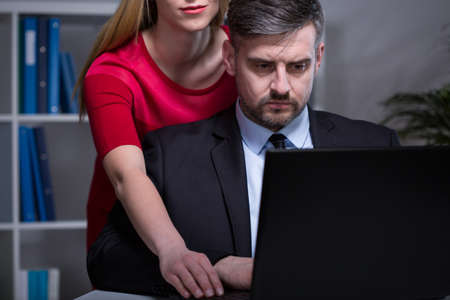 Handsome man working after hours with his young pretty secretary