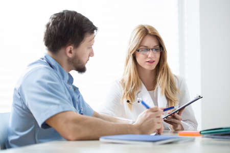 patient's history: Two young physicians consulting patients medical history Stock Photo