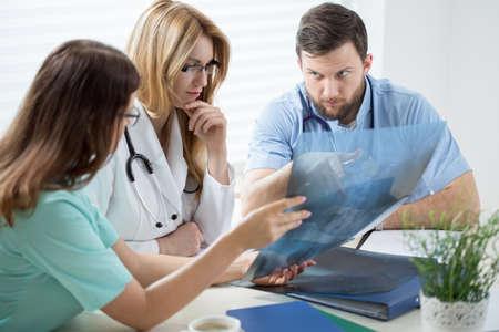 consulta médica: Tres jóvenes médicos en la consulta médica en el consultorio