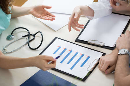 health check: Close-up of three physicians looking at test results Stock Photo