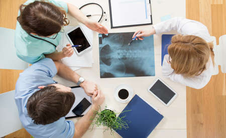 spinal column: Three young physicians looking at xray of spinal column